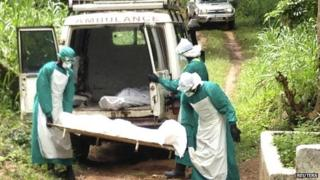 Health workers carry the body of an Ebola victim in Sierra Leone - 25 June 2014