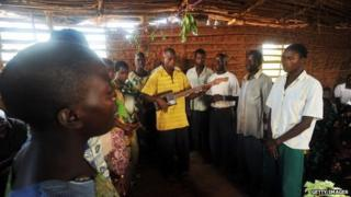 A man plays a guitar made out of wood and a empty can of oil while leading others in song during a prayer service at a church in Mutambara, Burundi - 2010