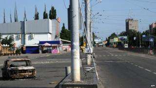 An empty street and a burned-out car near a bus station in Luhansk (12 July 2014)
