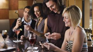 A group of people at a bar using their smartphones.