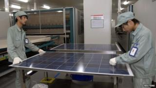 Workers in China holding solar panels