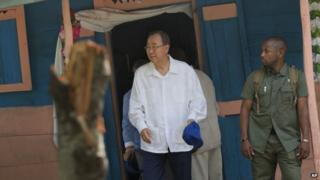 UN Secretary-General Ban Ki-moon walks out after visiting the house of a cholera victim during the launching of sanitation campaign in Hinche, Haiti, Monday, July 14, 2014.