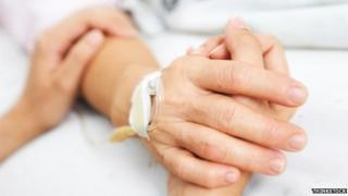 Two people holding hands in hospital bed
