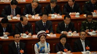 Delegates take part in the closing session of the National People's Congress (NPC) at the Great Hall of the People in Beijing on 13 March 2014.