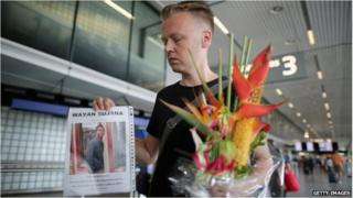 Dutchman Arthur Laumann holds a floral tribute and photograph of family friend Wayan Sujana of Bali