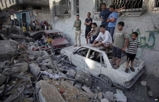 Palestinians look at the damage of a destroyed house in Rafah refugee camp, southern Gaza Strip