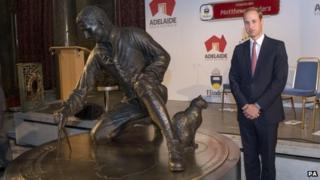 Prince William looks at a statute in honour of Captain Matthew Flinders