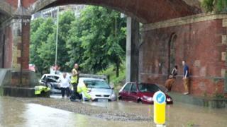 Cars stuck in flood water under a bridge
