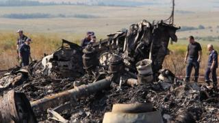 Ukrainian workers inspect debris at the main crash site of the Boeing 777 Malaysia Airlines flight MH17 on 20 July 2014