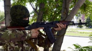 Pro-Russian militant aims Kalashnikov during combat with Ukrainian forces in eastern Ukrainian city of Donetsk. 21 July 2014