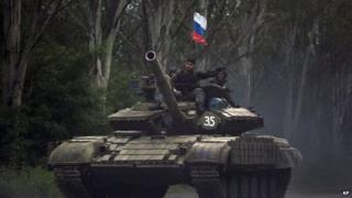 Pro-Russian rebels ride on a tank flying Russia's flag, on a road east of Donetsk, Monday