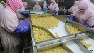 Workers processing meat at Shanghai Husi Food Co