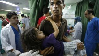 A Palestinian man carries a child, apparently wounded in an Israeli strike on a compound housing a UN school in Beit Hanoun, in the northern Gaza, into the emergency room of the Kamal Adwan hospital in Beit Lahiya, Thursday 24 July 2014