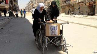 "Residents of Syria""s Yarmuk Palestinian refugee camp, south of Damascus, use a wheelchair to carry a box of goods distributed by the United Nations Relief and Works Agency (UNRWA) on July 17"