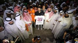 Supporters of Kuwaiti opposition leader and former MP Mussallam al-Barrak (portrayed on the shirt) take part in a demonstration to ask for his release