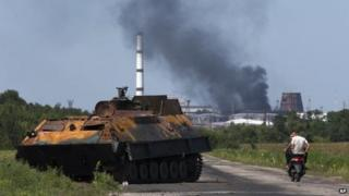 People ride a scooter past a destroyed military vehicle near the city of Lisichansk, Luhansk region, eastern Ukraine