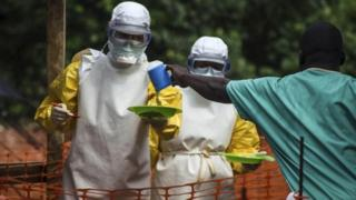 Medical staff working prepare to bring food to patients kept in an isolation area at an Ebola treatment centre in Kailahun, eastern Sierra Leone on 20 July 2014