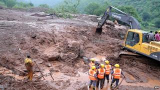 Rain is hampering efforts to search for scores of people presumed trapped under the mud and debris