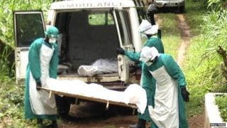 Health workers carry the body of an Ebola virus victim in Kenema, Sierra Leone, 25 June 2014