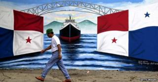Man walking past mural of panama flag