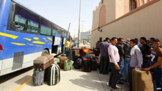 Egyptian workers prepare to board a bus in Tripoli as they are evacuated from Libya (31 July 2014)