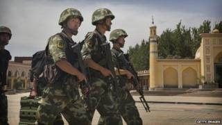 Chinese soldiers march in front of the Id Kah Mosque, China's largest, on 31 July 2014 in Kashgar, China