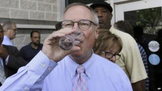 Toledo Mayor D Michael Collins drinks a glass of tap water after a news conference in Toledo, Ohio, 4 August 2014
