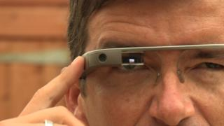 A close up of William wearing the Google Glass. The glass screen goes directly across his eye and his is pressing a button at the side of the glass