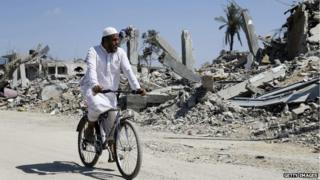 A Palestinian man rides past destroyed houses in Khuzaa town in southern Gaza