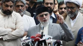 Muhammad Tahirul Qadri, Sufi cleric and leader of political party Pakistan Awami Tehreek (PAT) gestures as he addresses a news conference outside his residence in Lahore August 9