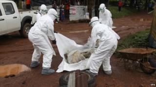 Liberian nurses remove a victim of Ebola near Monrovia, Liberia, 8 August 2014