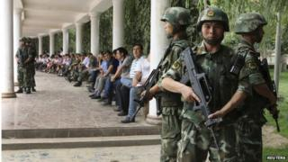 """Paramilitary policemen stand guard during a ceremony to award those who the authorities say participated in """"the crackdown of violence and terrorists activities"""" in Hotan, Xinjiang 3 August 2014"""