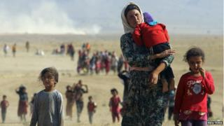Displaced people from the minority Yazidi sect, fleeing violence from forces loyal to the Islamic State in Sinjar town, walk towards the Syrian border, on the outskirts of Sinjar mountain, near the Syrian border town of Elierbeh of Al-Hasakah Governorate August 11, 2014.