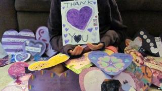 "A 12-year-old Waukesha, Wis., girl who wished to remain unidentified, holds a ""Thank You"" poster for the many supporters from around the world that have sent her cards 19 June 2014"