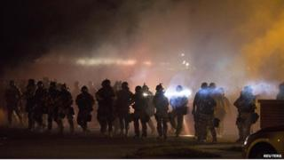 Heavily armed riot police clear demonstrators from a street in Ferguson, Missouri - 13 August 2014
