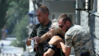 Local men help a wounded woman in Donetsk