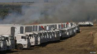 Smoke from a burning grass rises over the Russian convoy