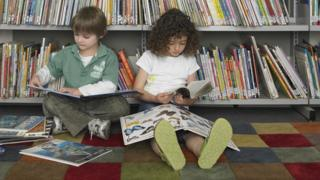Two children sit and read