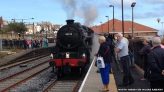 People waiting at the platform for steam train