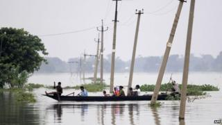 Indian villagers paddle a boat through floodwaters over submerged roads in Balimukh village in the Morigaon district of Assam state on August 17, 2014.