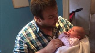 Sam Slater cradles baby