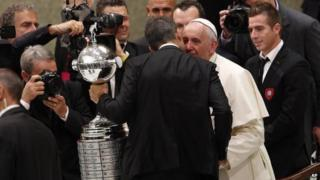 Pope Francis greets San Lorenzo football team players holding the Copa Libertadores they won last week at the Vatican on 20 August, 2014