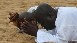 Liberians pray on the beach on 20 August 2014 in Monrovia for help in dealing with the Ebola crisis