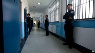 Police guards stand in a hallway inside the No.1 Detention Center during a government guided tour in Beijing on 25 October 2012.