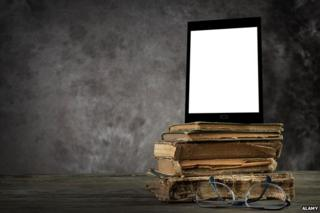 Tablet propped up on top of old books