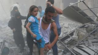 A Syrian man carries a girl amid debris following a air strike by government forces in the northern city of Aleppo on 15 July