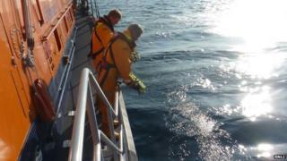 RNLI putting wreath in sea