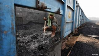 A worker unloads coal from a goods train at a railway yard in the northern Indian city of Chandigarh
