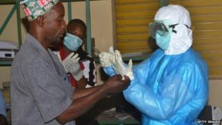 Health workers in protective suits.