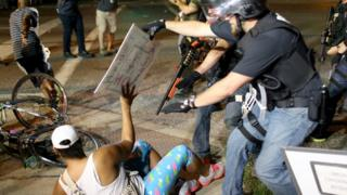 A protestor in Ferguson, Missouri is confronted by a police officer weilding a shotgun.